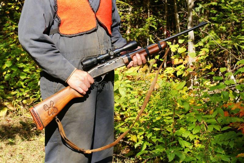 与步枪的猎人在森林 免版税库存照片