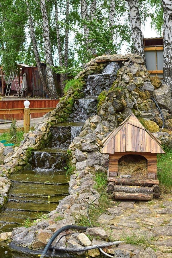 与步的瀑布与小屋在公园 图库摄影