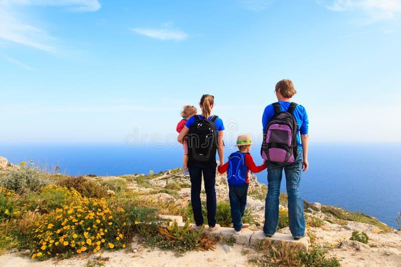 与步行在夏天山的孩子的家庭 免版税库存照片