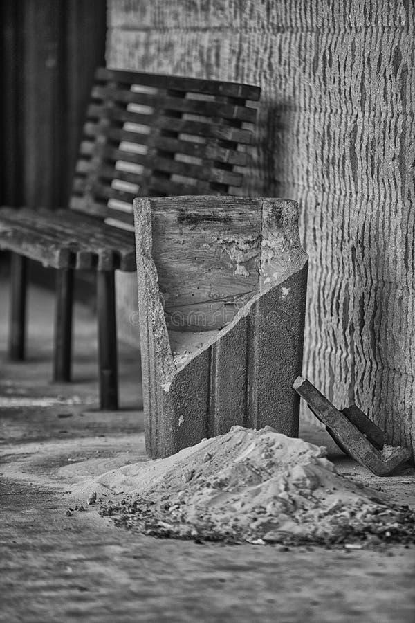 与残破的具体烟灰缸的公开长凳 免版税库存图片