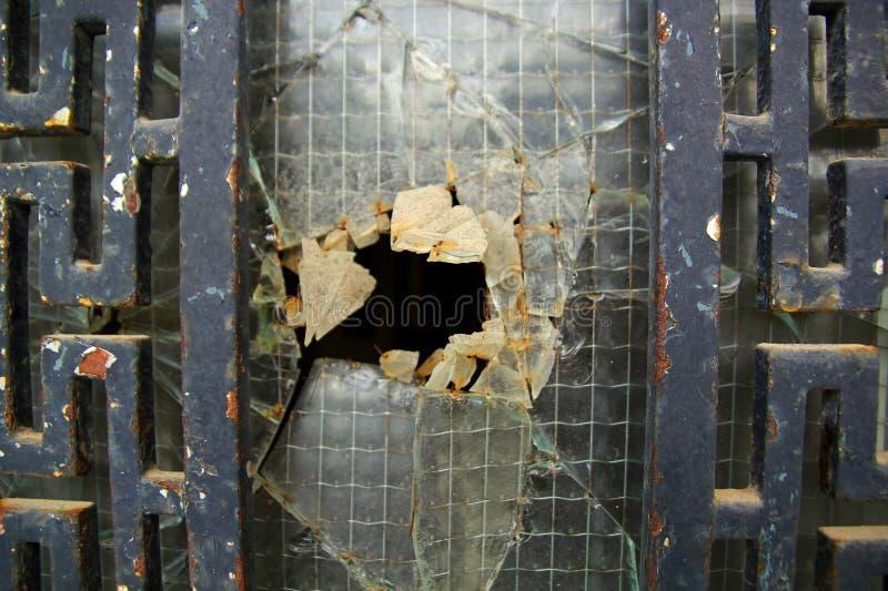 与残破的玻璃的老生锈的门 免版税图库摄影