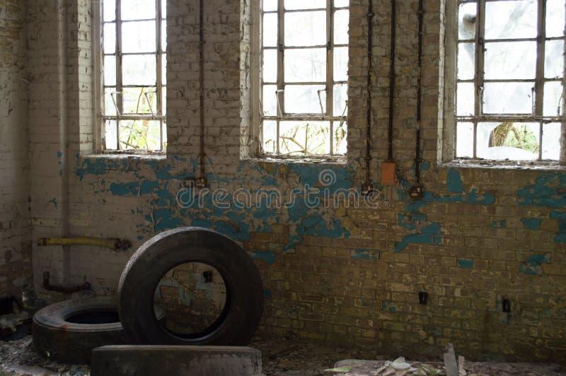 与残破窗口,削皮油漆和三的一个老遗弃大厦使用了轮胎 免版税库存图片