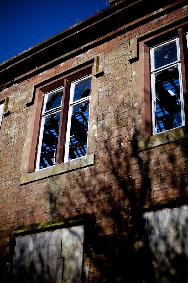 与残破的窗口的遗弃砂岩大厦 库存照片
