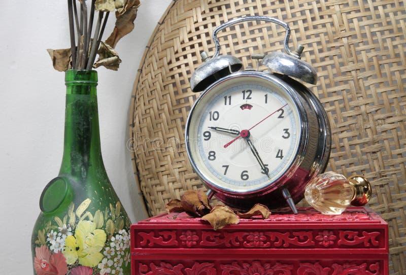 与残破的闹钟,有死的ros的老玻璃花瓶的静物画 免版税库存照片
