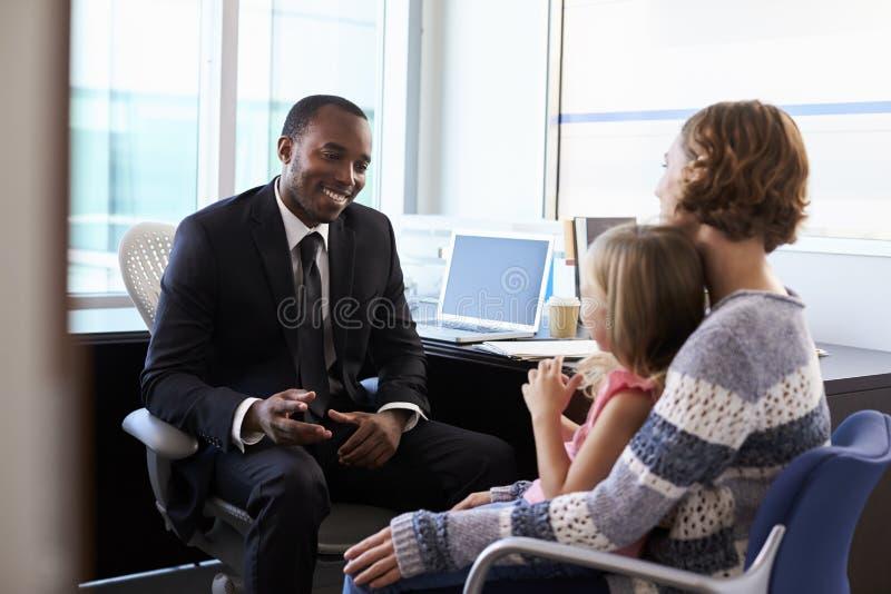 与母亲和孩子的儿科医生会谈在医院 图库摄影