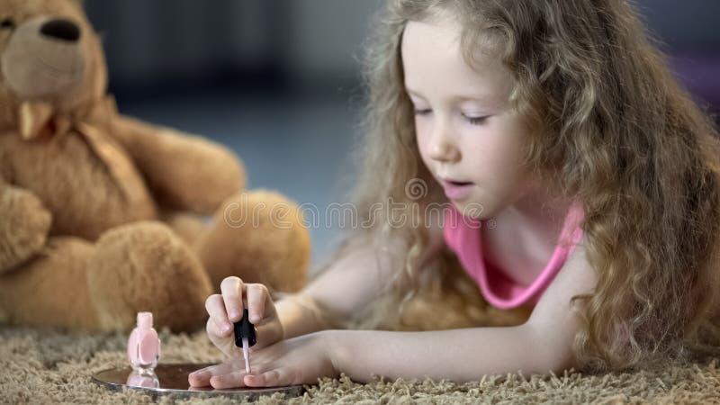 与母亲擦亮剂的被集中的女孩绘的钉子,假装是更老 库存图片