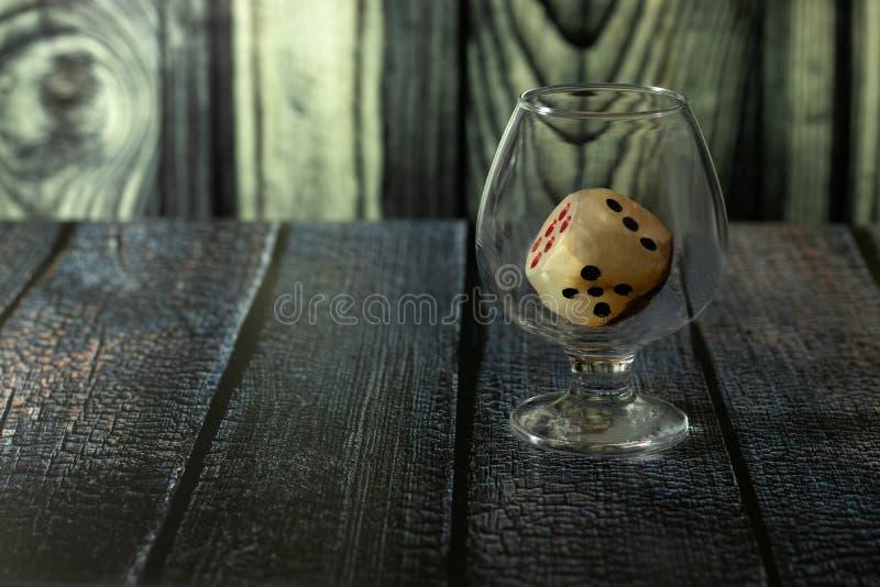 与比赛立方体的玻璃在桌上站立 库存图片