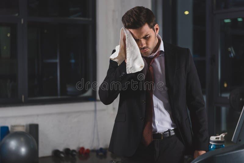 与毛巾的疲乏的满身是汗的商人在体育 免版税库存照片