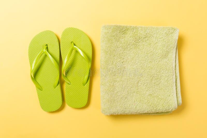 与毛巾的绿色触发器在与拷贝空间的黄色背景顶视图舱内甲板位置 假日假期与海滩海的旅行概念 库存照片