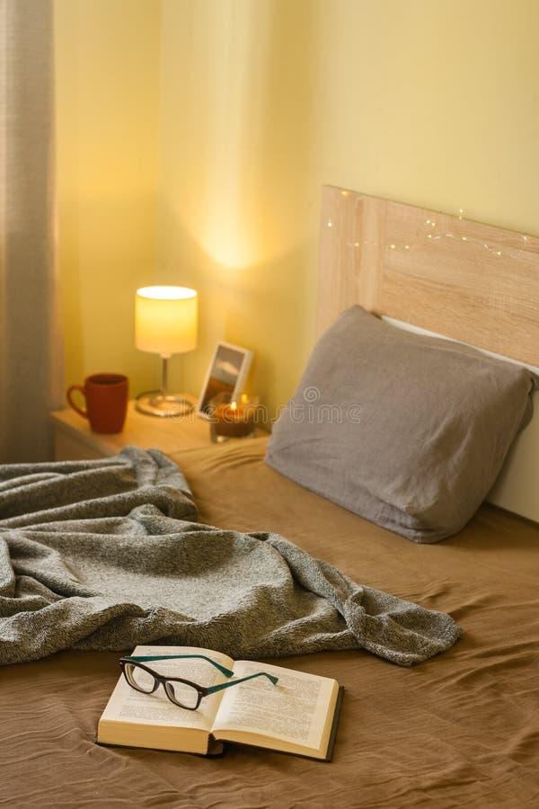 与毯子、开放书与玻璃和温暖的光的卧室舒适内部 免版税库存照片