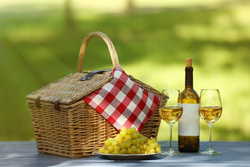 与毯子、酒和葡萄的柳条筐在桌上在公园 库存图片