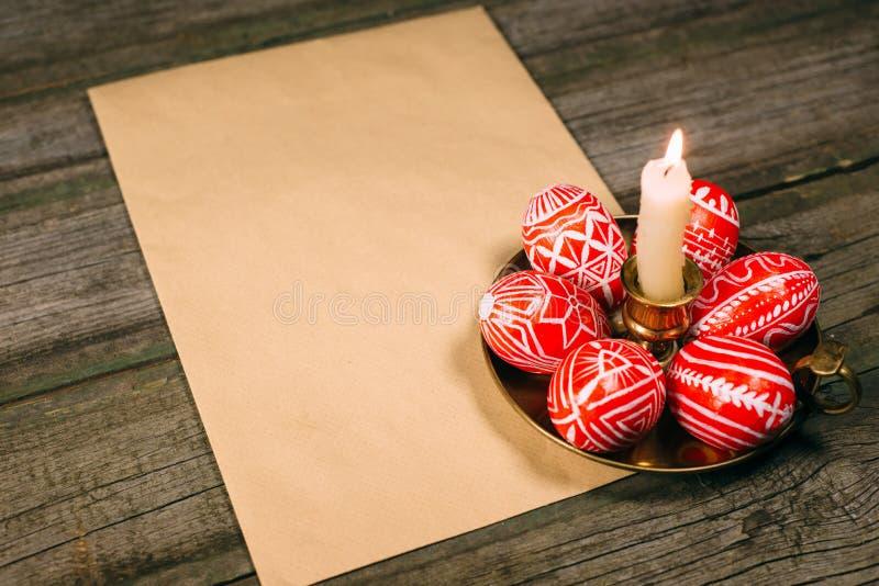 与民间白色样式的特写镜头复活节红色鸡蛋在有灼烧的蜡烛的黄铜烛台放置,在土气木头t的纸旁边 库存照片