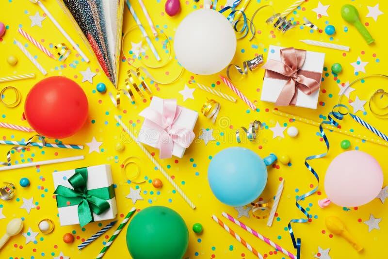 与气球、礼物、五彩纸屑、狂欢节盖帽、星、糖果和飘带的生日聚会背景 平的位置样式 五颜六色的看板卡 库存照片