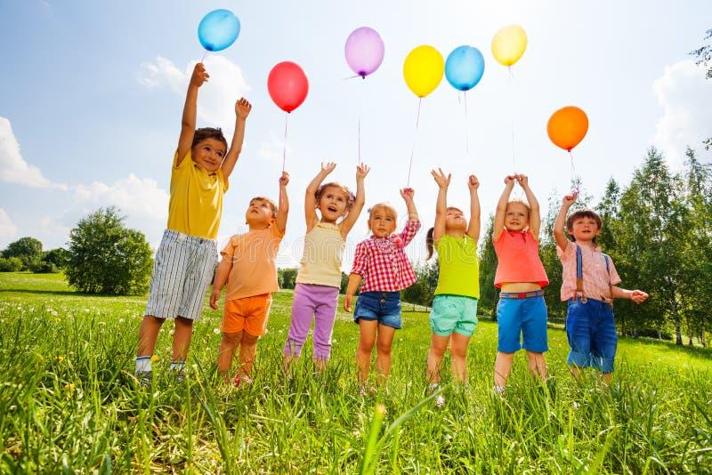 与气球和胳膊的愉快的孩子在天空 免版税库存照片