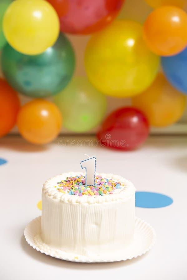 与气球墙壁的第一生日蛋糕 图库摄影