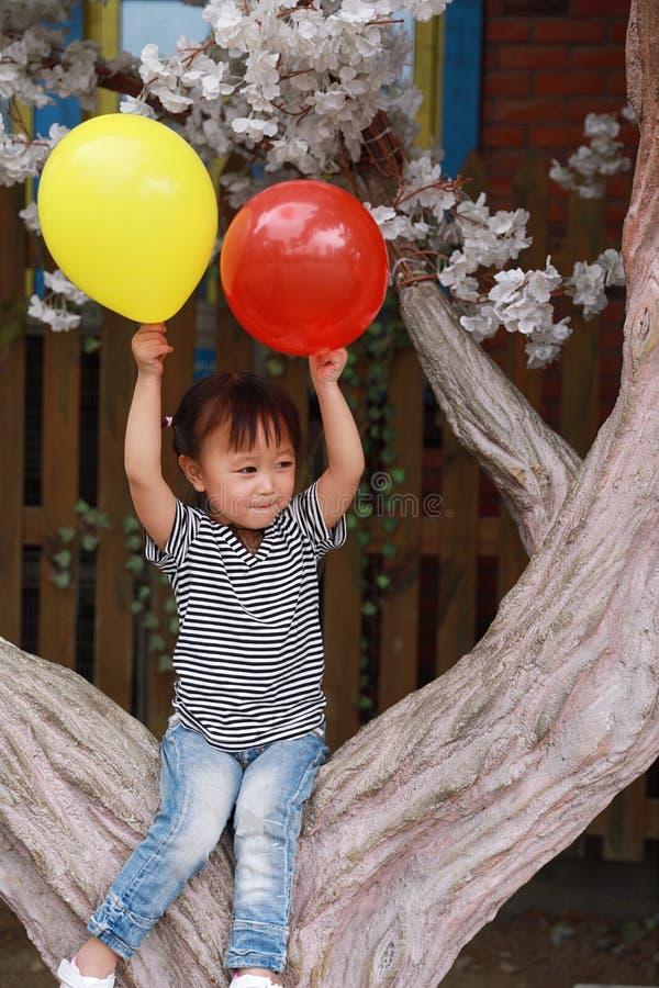 与气球的亚洲中国逗人喜爱的淘气可爱的可爱的女孩戏剧和由树坐获得室外的乐趣在夏天公园愉快的微笑 免版税库存照片