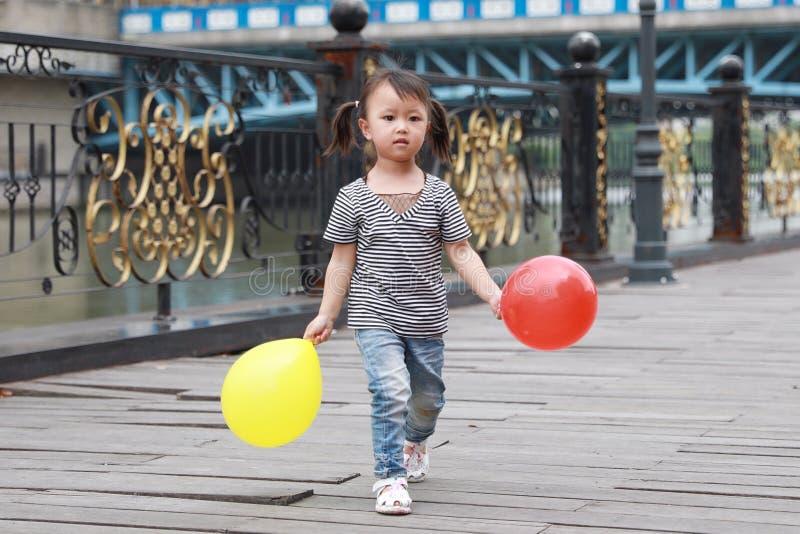 与气球的亚洲中国逗人喜爱的淘气可爱的可爱的女孩戏剧和获得室外的乐趣在街道上的夏天公园愉快的微笑步行 免版税库存图片