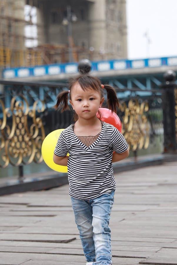 与气球的亚洲中国逗人喜爱的淘气可爱的可爱的女孩戏剧和获得室外的乐趣在街道上的夏天公园愉快的微笑步行 库存图片