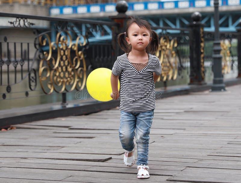 与气球的亚洲中国逗人喜爱的淘气可爱的可爱的女孩戏剧和获得室外的乐趣在街道上的夏天公园愉快的微笑步行 免版税图库摄影