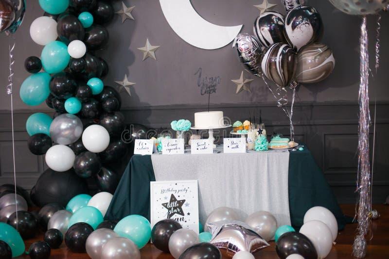与气球的时髦的装饰的儿童棒棒糖在生日聚会 免版税库存图片