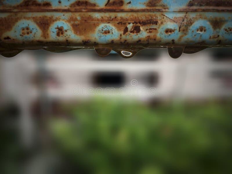 与水下落的老钢方形的管铁锈在庭院 库存图片