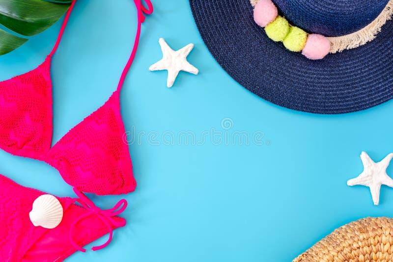 与水军蓝色帽子、桃红色比基尼泳装、太阳镜和贝壳的夏天蓝色横幅在蓝色背景顶视图 库存照片