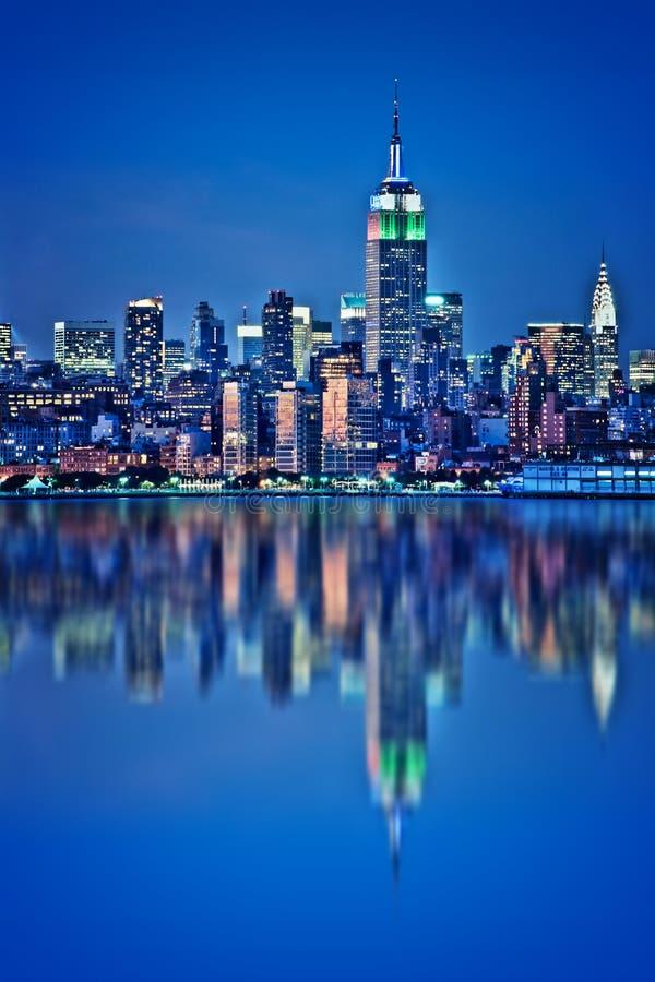 与水反射的纽约地平线在晚上 库存照片