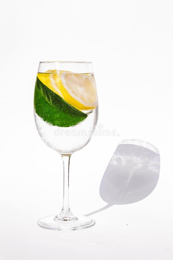 与水和柠檬的湿玻璃 柠檬树叶子 酷暑饮料 健康有机食品背景 免版税图库摄影
