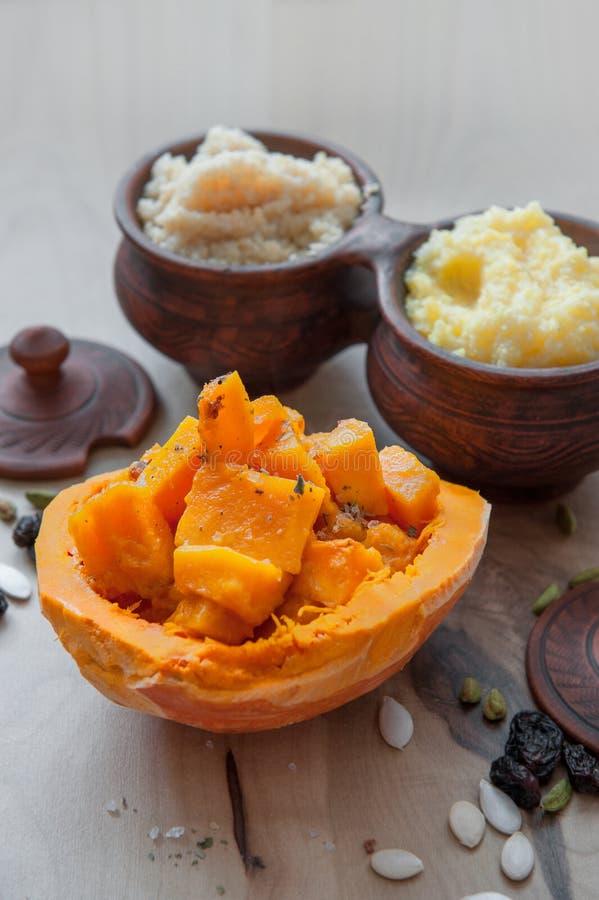 与水多的烤南瓜大明亮的橙色片断的素食麦子粥  库存照片