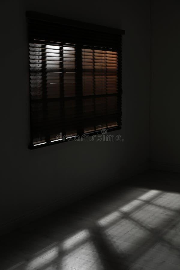 与水平的窗帘的窗口在暗室 免版税库存图片