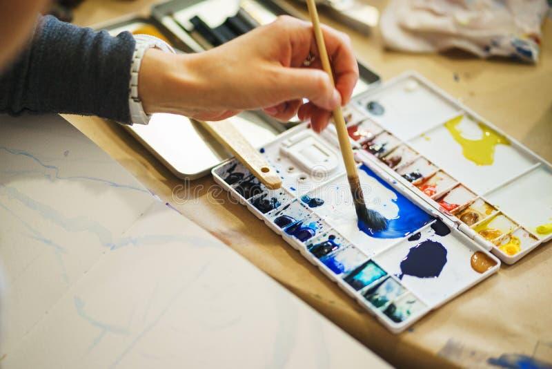 与水彩的艺术家油漆和揉在塑料调色板的油漆 免版税库存照片