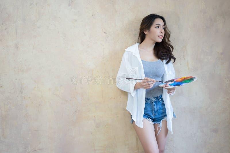 与水彩调色板的侧视图年轻亚洲妇女画象 免版税库存照片