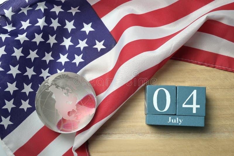 与水晶玻璃地球的美国旗子和在木背景的木日历 库存图片