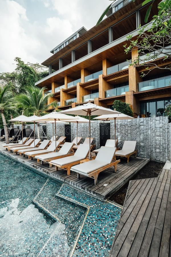 与水池、室外日光浴椅子和伞的现代建筑学手段 在泰国放松和隐藏地方 免版税库存照片