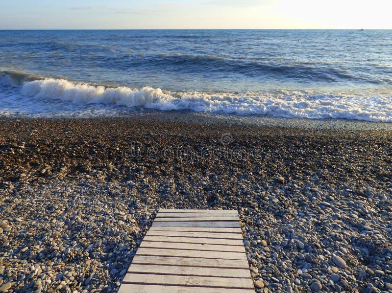 与水波和小卵石的沿海 库存照片