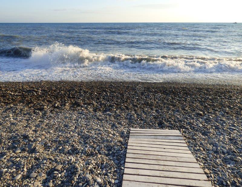 与水波和小卵石的沿海 图库摄影
