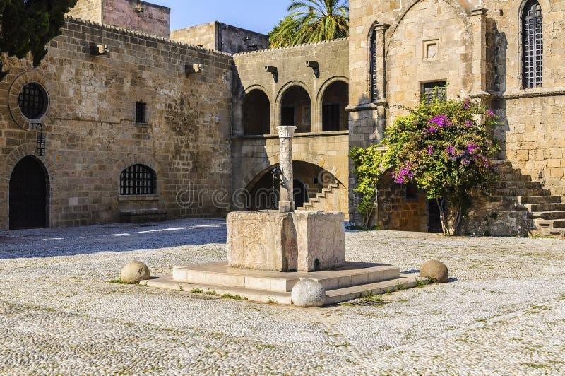 与水的水源的中世纪方形的Argirokastro 罗得岛老镇,希腊 库存照片