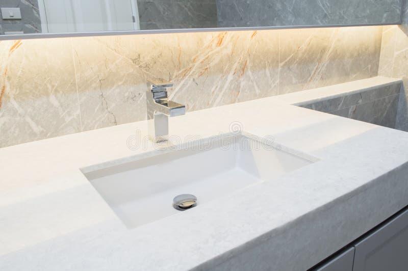与水盆的桌面白色大理石 墙壁和地板灰棕色、休息室灰色大理石石室内设计或洗手间背景 ? 库存照片