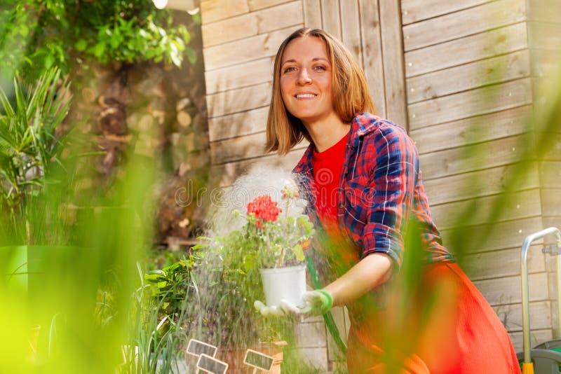 与水管喷水隆头的妇女浇灌的庭院花 库存照片