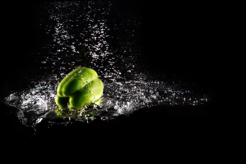 与水飞溅的新鲜的绿色被隔绝的甜椒和泡影 胡椒拷贝空间 水多的绿色辣椒粉下降了落入水 免版税库存图片