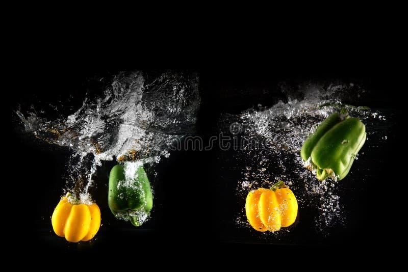 与水飞溅的新鲜的绿色,黄色喇叭花被隔绝的胡椒和泡影 小组健康拷贝空间辣椒粉  色的辣椒粉 免版税库存图片