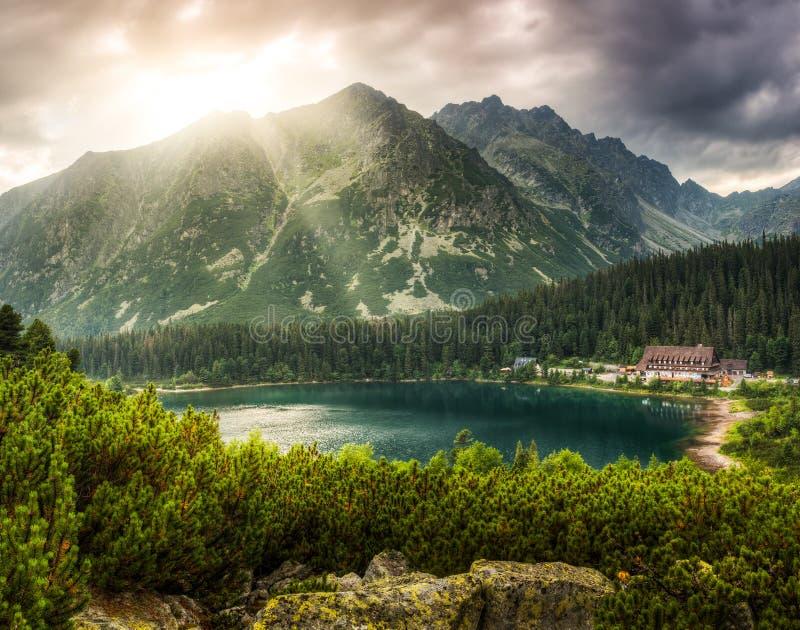 与池塘和山瑞士山中的牧人小屋的山风景 库存图片