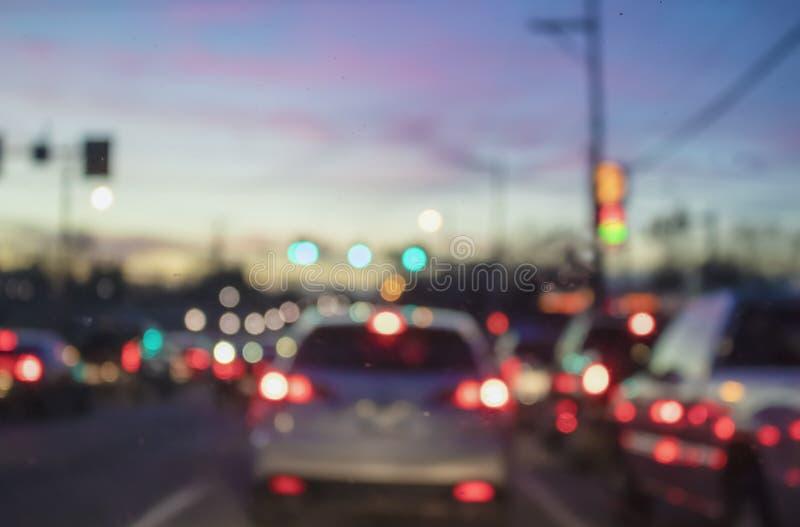 与汽车和电杆的被弄脏的bokeh城市交通背景反对日落天空 库存图片