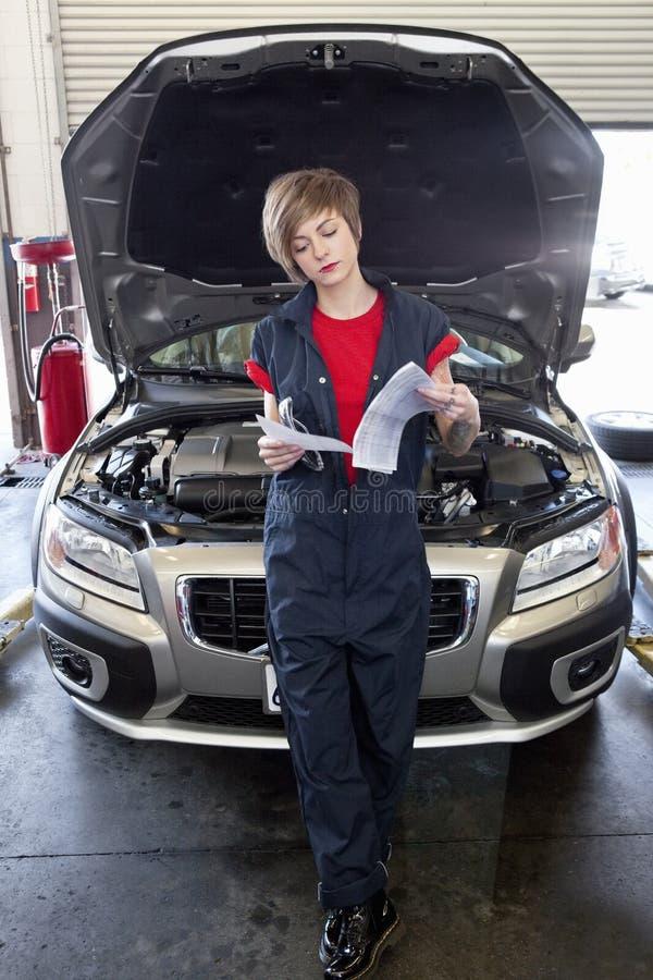 与汽车开放帽子的年轻女性技工读书纸在车库的 图库摄影