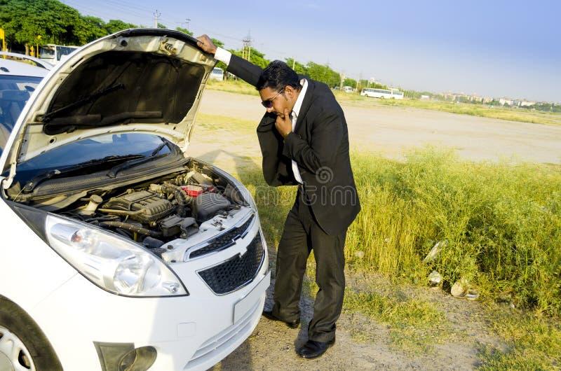 与汽车故障的失去的商人 库存图片