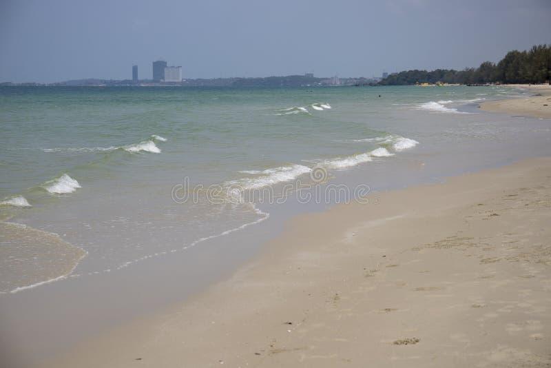 与沙子海滩和遥远的大厦的海滨 与白色沙子海滩的田园诗海视图 免版税库存照片