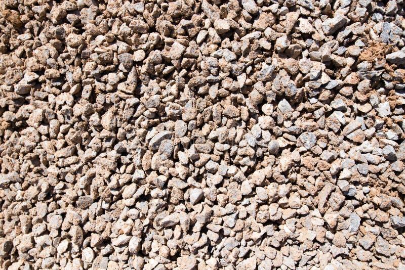 与沙子的被击碎的石头作为背景 免版税库存照片