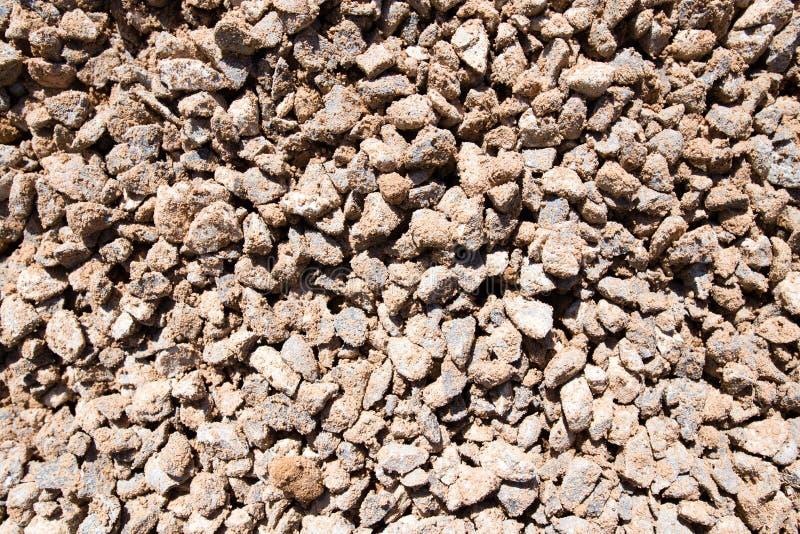 与沙子的被击碎的石头作为背景 库存照片