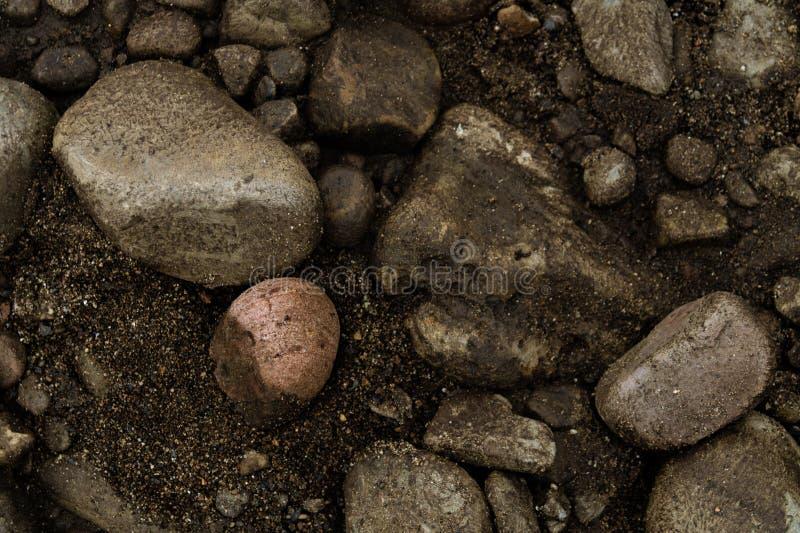 与沙子纹理被拍摄的从上/与石头和沙子微粒的背景的岩石 库存图片