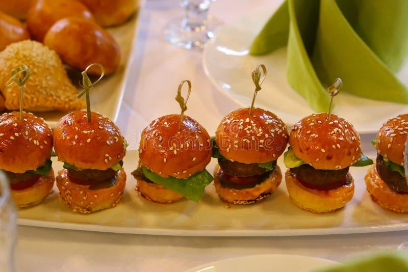 与沙拉叶子的微型汉堡包在板材服务图片